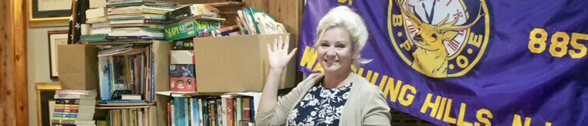 Candace standing in front of the book collection at Watchung Hills Elks Lodge 885